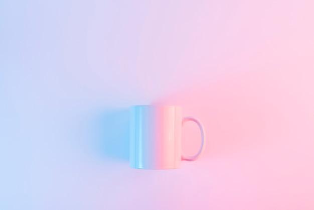 Caneca de café cor-de-rosa contra o fundo cor-de-rosa com copyspace para escrever o texto Foto gratuita