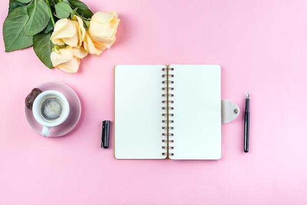 Caneca de café da manhã no café da manhã, caderno vazio, lápis e rosa Foto Premium