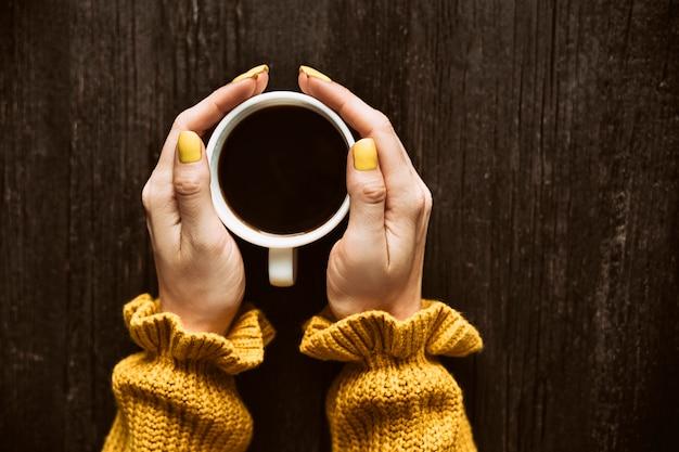 Caneca de café em uma mão feminina. Foto Premium