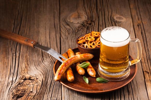Caneca de cerveja com linguiça e lanches na placa de madeira Foto gratuita