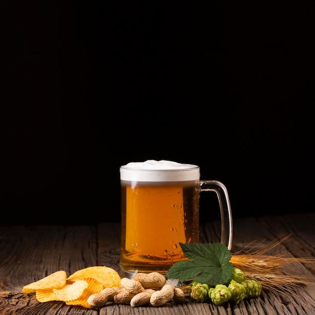 Caneca de cerveja de close-up com lanches Foto gratuita