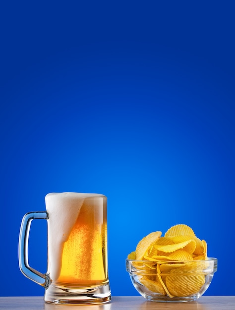 Caneca de cerveja light com espuma e batatas fritas no fundo azul Foto Premium