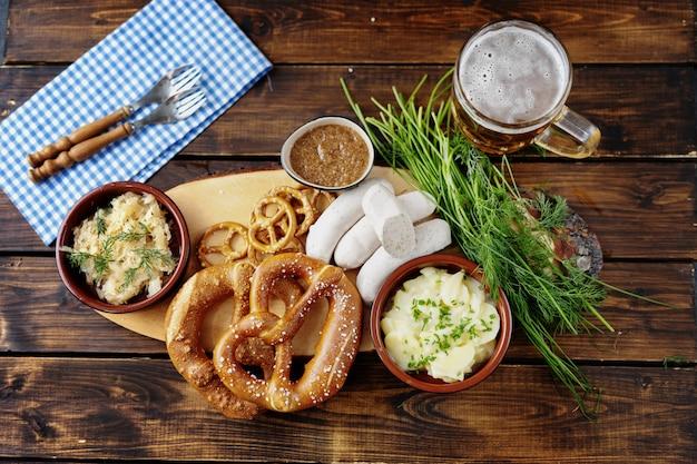 Caneca de cerveja, pretzels e salsichas na mesa de madeira. vista do topo Foto Premium