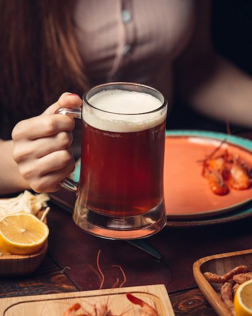 Caneca de cerveja vermelha com camarão e limão Foto gratuita