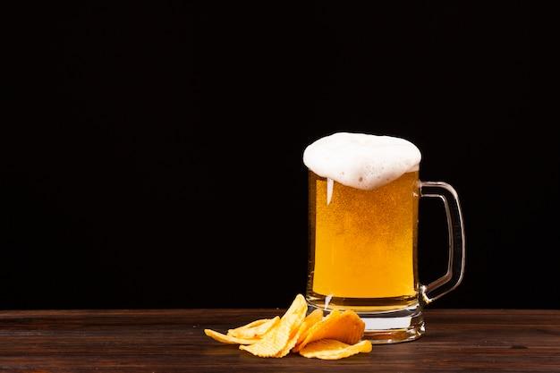 Caneca de cerveja vista frontal com batatas fritas Foto gratuita