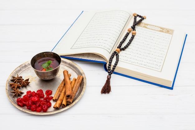 Caneca de chá perto de especiarias na bandeja e livro com miçangas Foto gratuita