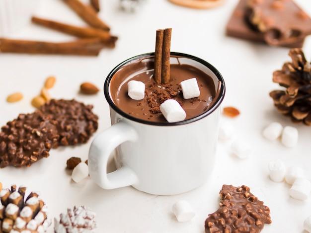 Caneca esmaltada de chocolate quente com canela e marshmallows Foto gratuita