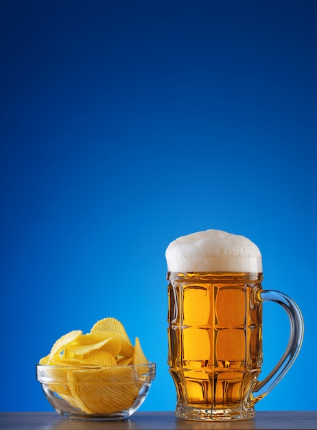 Caneca lapidada de cerveja light com espuma e batatas fritas no prato Foto Premium