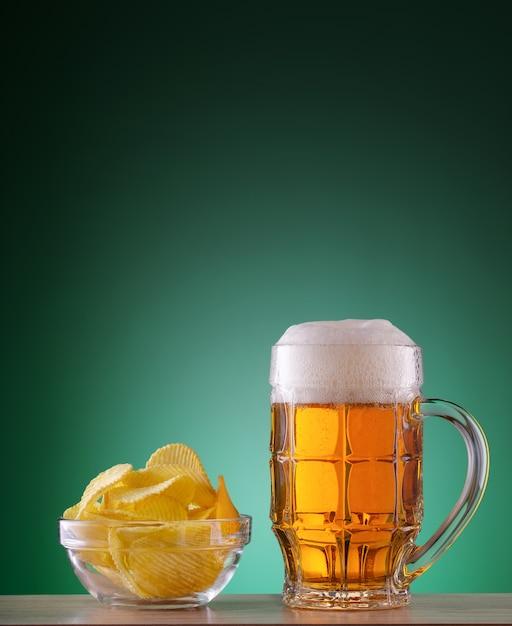 Caneca lapidada de cerveja light com espuma e batatas fritas Foto Premium
