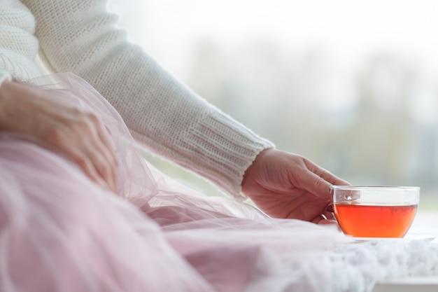 Caneca quente de chá com mãos de mulher na camisola de lã retrô Foto Premium