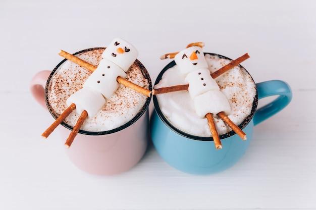 Canecas com chocolate quente nas quais os homens do marshmallow relaxam. conceito de um casal Foto Premium