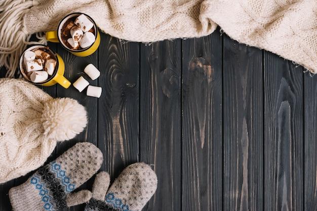 Canecas com marshmallows perto de desgaste quente Foto gratuita