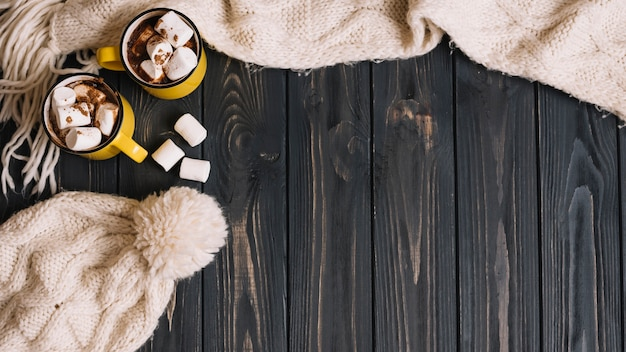 Canecas com marshmallows perto de roupas quentes Foto gratuita