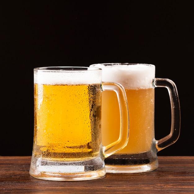 Canecas de cerveja com espuma na placa de madeira Foto Premium