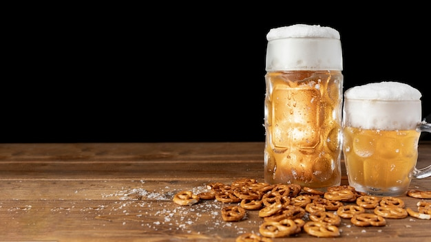 Canecas de cerveja com pretzels em uma mesa Foto Premium