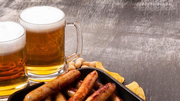 Canecas de cerveja e salsichas em fundo escuro Foto gratuita