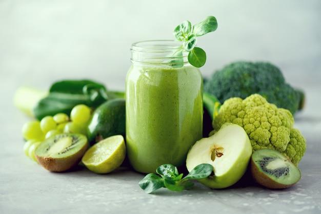 Canecas de vidro jar com smoothie de saúde verde, folhas de couve, limão, maçã, kiwi, uvas Foto Premium