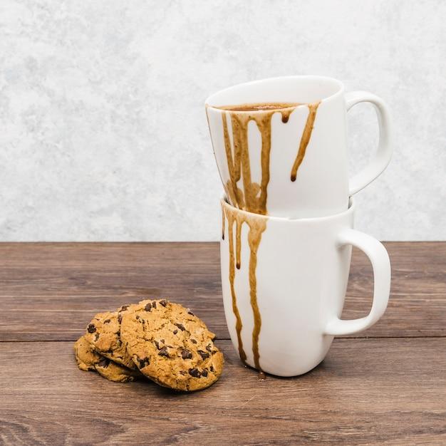 Canecas sujas de vista frontal com cookies Foto gratuita