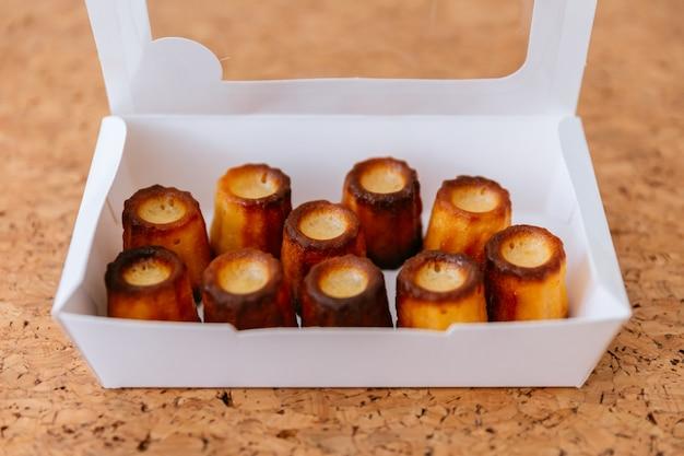 Canelés cozido fresco dentro da caixa de papel branco. Foto Premium