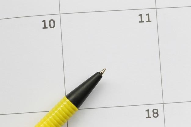 Caneta amarela é colocada no calendário no 11º dia e tem espaço de cópia. Foto Premium