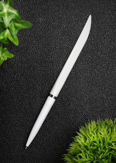 Caneta branca em fundo de couro preto. Foto Premium