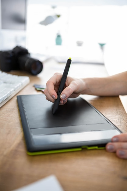 Caneta de desenho em um tablet de desenho digital no escritório Foto Premium