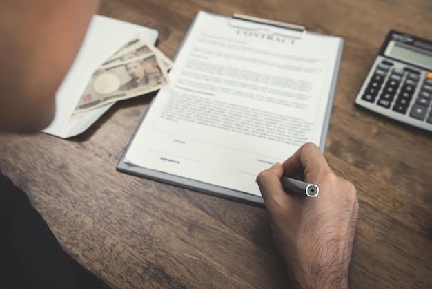 Caneta de exploração de mão assinando contrato com dinheiro, moeda iene japonês, em cima da mesa Foto Premium