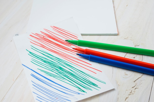 Caneta de ponta de feltro colorida e papel com traço de caneta na mesa de madeira branca Foto gratuita