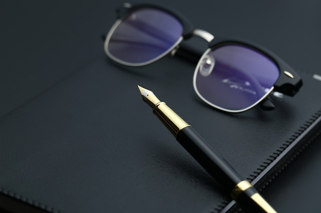 Caneta dourada, caderno, calculadora e óculos na mesa preta Foto gratuita