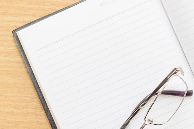 Caneta e caderno aberto com página em branco Foto Premium