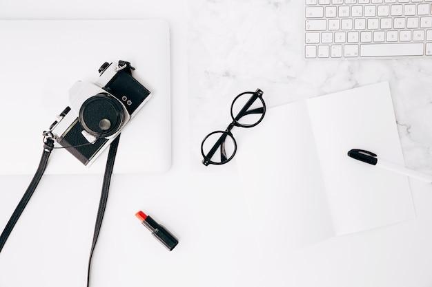 Caneta e óculos em papel; batom vermelho; câmera; teclado e tablet digital na mesa Foto gratuita