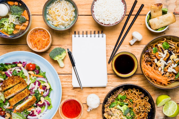 Caneta no bloco de notas em branco espiral rodeado com comida tailandesa tradicional na mesa de madeira Foto gratuita