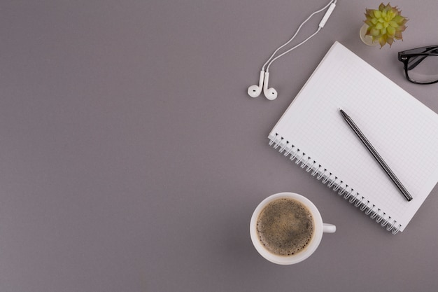 Caneta perto de bloco de notas, copo, fones de ouvido e óculos Foto gratuita