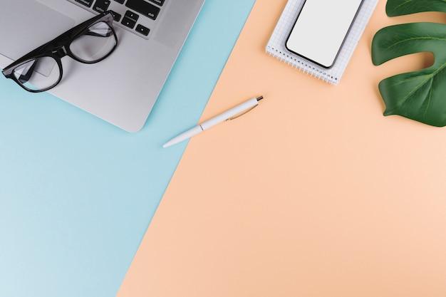 Caneta perto de bloco de notas, smartphone, planta, óculos e laptop Foto gratuita