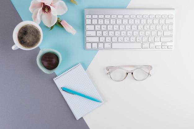 Caneta perto de caderno, xícara, biscoito, flor, óculos e teclado Foto gratuita