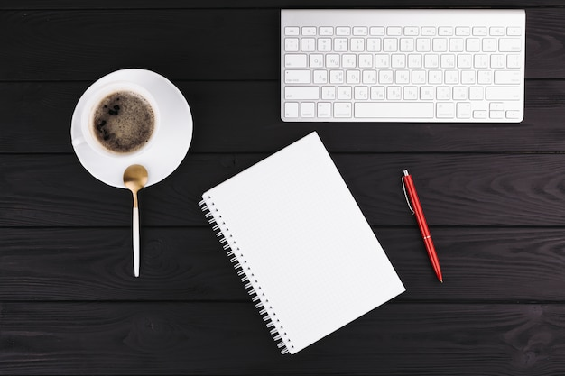 Caneta perto do bloco de notas, copo no prato, colher e teclado Foto gratuita