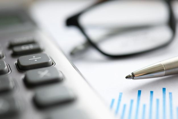 Caneta prata com gráfico de papel e óculos deite-se na mesa de escritório Foto Premium