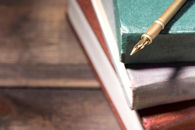 Caneta-tinteiro na pilha de livros antigos Foto Premium