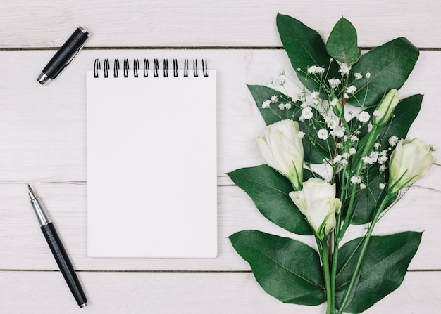 Caneta-tinteiro preta; bloco de notas espiral em branco; eustoma e gypsophila buquê de flores na mesa de madeira Foto gratuita