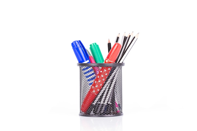 Canetas coloridas e lápis no suporte isolado no fundo branco Foto Premium