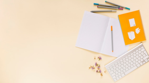 Canetas de feltro coloridas; flor; notebook com teclado sobre fundo colorido Foto gratuita