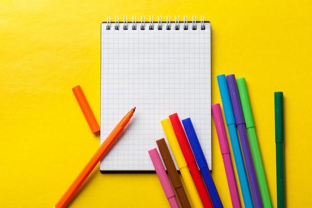 Canetas de feltro e bloco de notas em branco amarelo brilhante Foto Premium