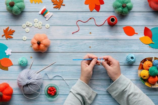 Canhoto em malha de crochê. vista superior da mesa de madeira com as mãos da canhota, bolas de lã, feixes de lã Foto Premium