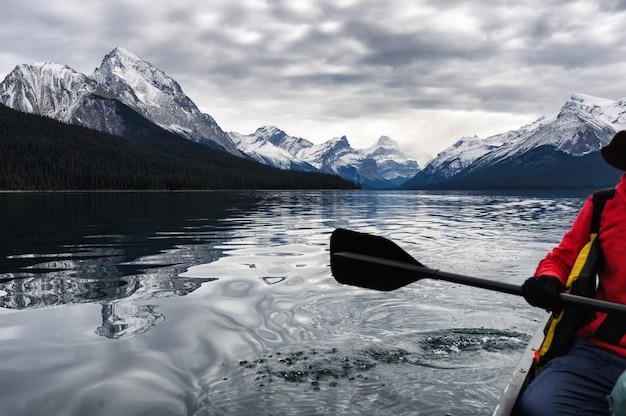 Canoagem de viajante vermelho e montanha rochosa no lago maligne Foto Premium