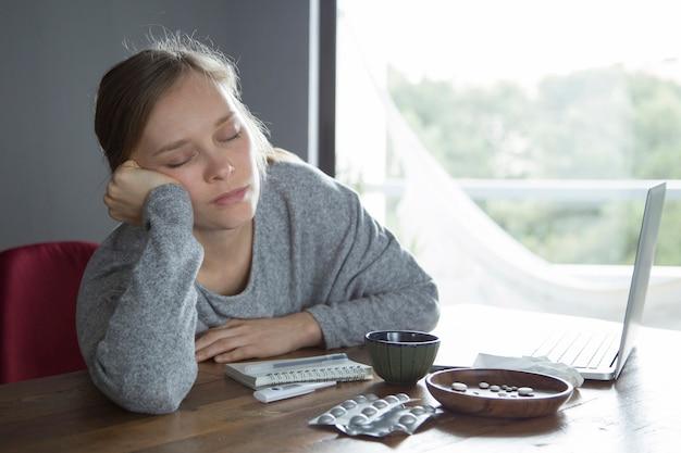Cansada mulher doente com os olhos fechados, relaxantes depois de trabalhar no pc Foto gratuita