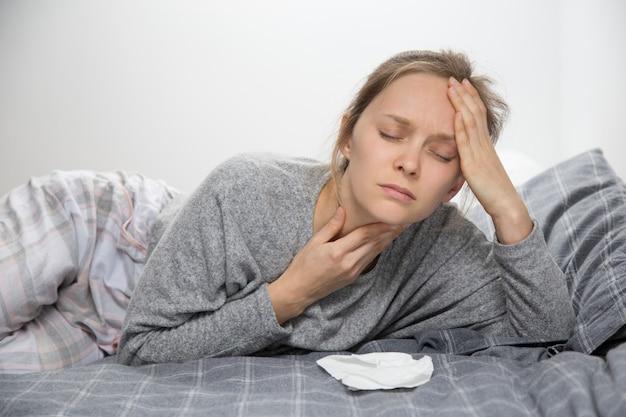 Cansada mulher doente na cama com os olhos fechados, com dor de garganta Foto gratuita