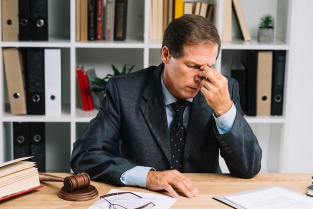 Cansado advogado maduro sentado no tribunal Foto gratuita