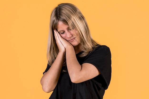 Cansado com sono mulher tira soneca magra na palma da mão na frente do pano de fundo amarelo Foto gratuita