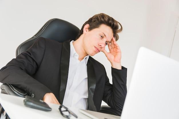 Cansado empresário sentado no escritório Foto gratuita