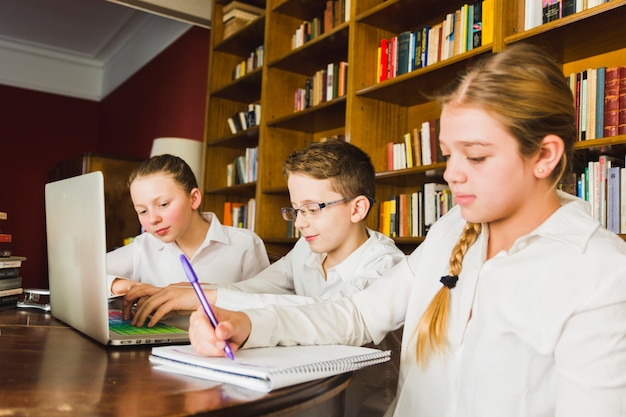 Cansado garota fazendo lição de casa com colegas Foto gratuita